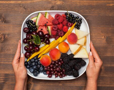 Hand with a plate full of summer fruits on wooden table - top view 免版税图像 - 130393347