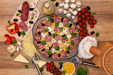 Pizza ready to be baked with all ingredients lying around on the table - top view
