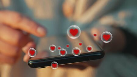 Woman hand browse or create popular content on smartphone screen, likes pouring as a swirl of red hearts icons. Viral trends concept - close up