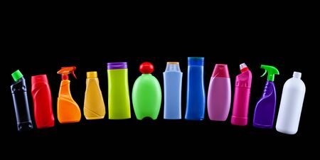 Plastic waste bottles in rainbow colors - widespread pollution concept - black background