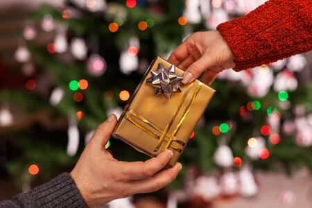 Hands with christmas present on blurry lights background - giving gifts in the holiday season concept 免版税图像 - 134276538