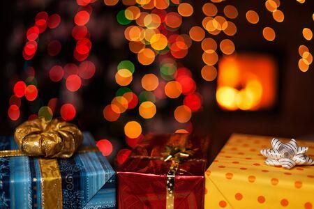 흐릿한 크리스마스 트리와 벽난로가 있는 어두운 배경에 아름다운 크리스마스 선물 - 휴일의 고요한 축복