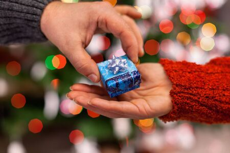 Hands of man and woman with small christmas gift on colorful blurry lights background - giving gifts in the holiday season