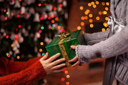Hands offer and receive beautiful wrapped christmas present on colorful blurry xmas lights background - close up