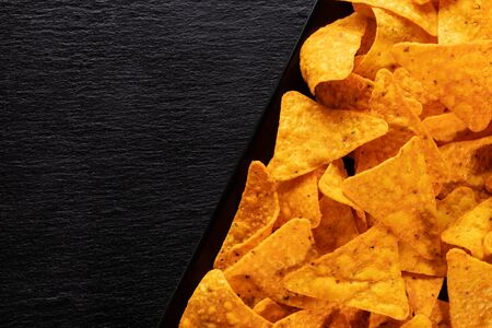 Delicious tortilla chips close up with copy space on black slate background 免版税图像
