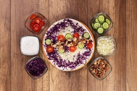 Making a kebab or gyros - a traditional roll sandwich wrapped in wheat flour wraps and various fresh ingredients - top view, flat lay 免版税图像 - 144354582