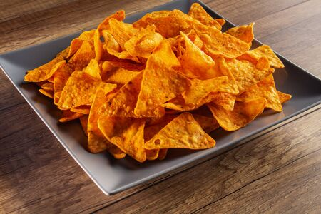 Delicious tortilla chips on a rectangular plate - close up of appetizing spicy corn flour triangles 免版税图像 - 143534567