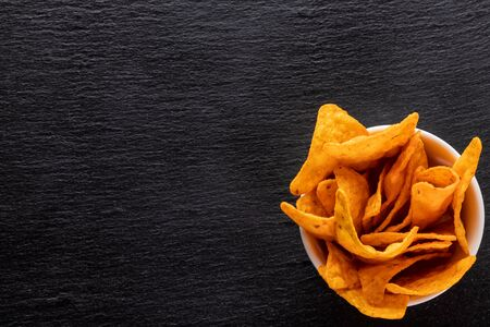 Tortilla chips in small serving cup on black slate background - top view, copy space 免版税图像