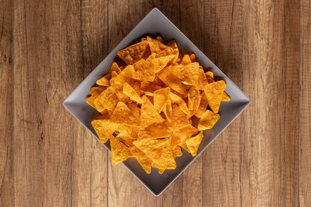 Delicious tortilla chips on a rectangular plate - close up of appetizing spicy corn flour triangles, top view 免版税图像
