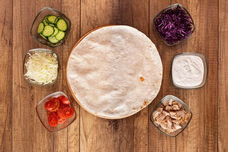Making a kebab or gyros - a traditional roll sandwich wrapped in wheat flour wraps and various fresh ingredients - top view, flat lay with copy space in center 免版税图像 - 144354583