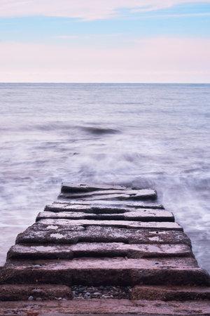 Long stone sea pier breakwater goes deep into distance and waves break on it. Frozen photo using long shutter speed. Beautiful sea landscape.