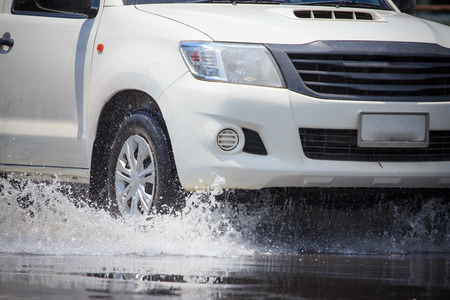 Splash by a car as it goes through flood water photo