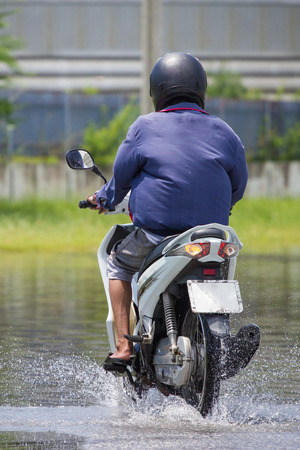 Splash by a motorcycle as it goes through flood water photo