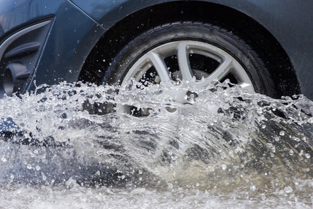 drain fly: Car splashes through a large puddle on a flooded street Stock Photo