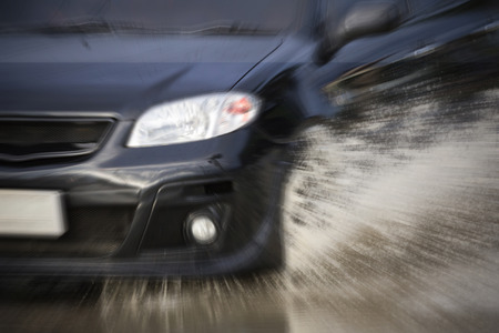 big water splash with car on flooded road after rains