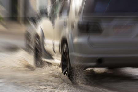 water splash with car on flooded road after rains