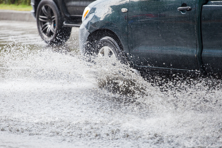 downpour: Car splashes through a large puddle on a flooded street Stock Photo