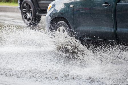 salpica coche a través de un gran charco en una calle inundada Foto de archivo