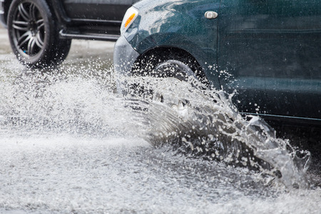 Car splashes through a large puddle on a flooded street Stock Photo