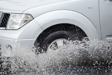 hydroplaning: Car splashes through a large puddle on a flooded street Stock Photo