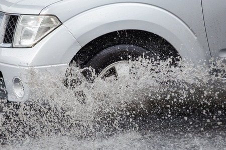 hydroplaning: Splash by a car as it goes through flood water