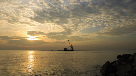 Clouds spread across the sky before sunset at Bangpu seaside, gulf of thailand with Cargo ships sail past at evening times.