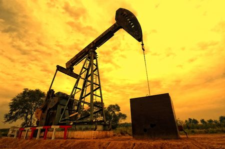 Oil pumping Unit at sunset time Stock Photo - 5540080