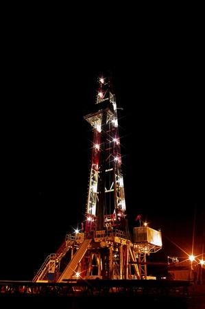 pozo petrolero: Torre de perforaci�n en la noche Foto de archivo
