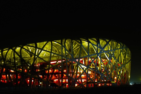 each year: Beijing, China - April 26, 2011: The Beijing National Stadium( the Birds Nest) lights up. As a landmark of modern China, which attracting million of tourists each year.