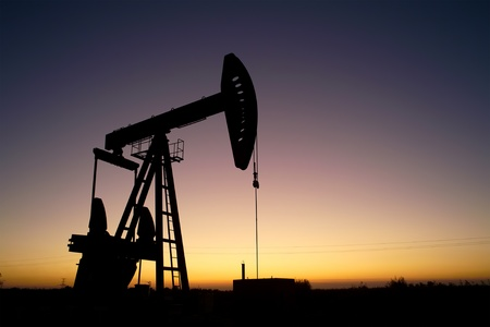 Pump jack silhouette at sunset photo