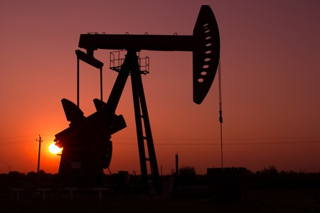 Pump jack silhouette at sunset Stock Photo