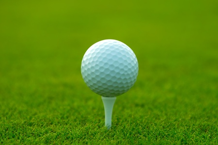 Golf ball and tee on green grass photo