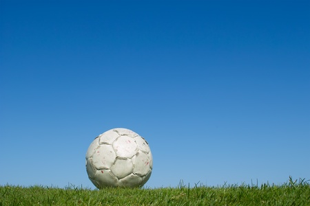 Dirty old soccer ball on grass photo