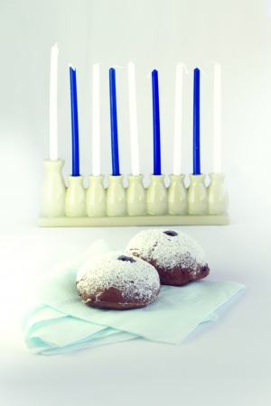 jewish cuisine: Jelly doughnuts and  a Hanukka menorah with blue and white candles
