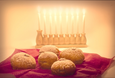 Lit Hanukka menorah with jelly doughnuts in foreground  photo