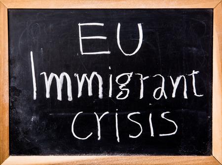 immigrant: eu immigrant crisis word on blackboard Stock Photo