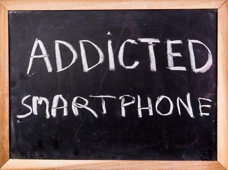 addicted: addicted smartphone  word on blackboard