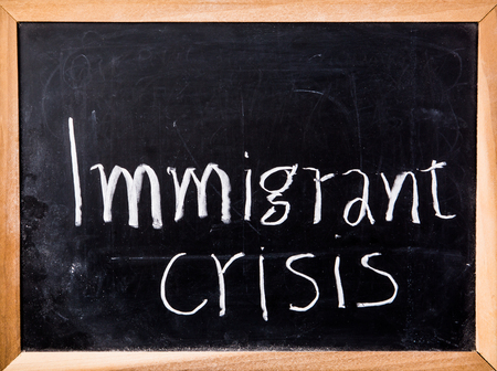 immigrant: immigrant crisis word on blackboard Stock Photo
