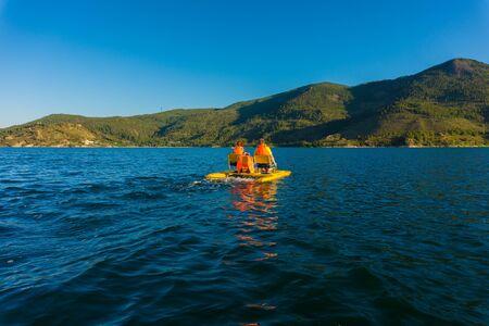 Bella vista di un'interessante passeggiata di persone che si riposano, su un catamarano, su un lago, fiume, nella natura in una giornata estiva