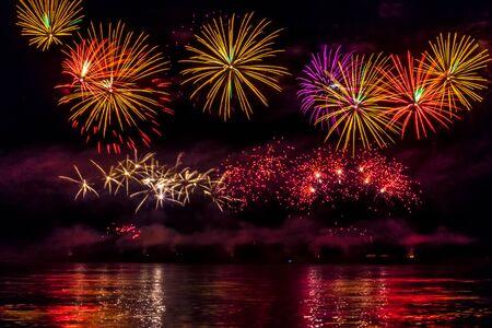 Fuegos artificiales festivos brillantes reflejados en el río