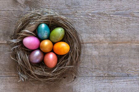 Beautiful multi-colored Easter eggs lie in a nest on a old wooden background, Easter holiday, copy space