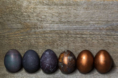 Colored painted pearl chicken Easter eggs of violet, golden color on a old wooden background, Easter holiday, copy space