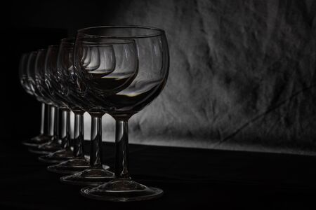 Set of multiple glasses shot in low-key lighting over the black background. Smooth lines and shapes. Concept.