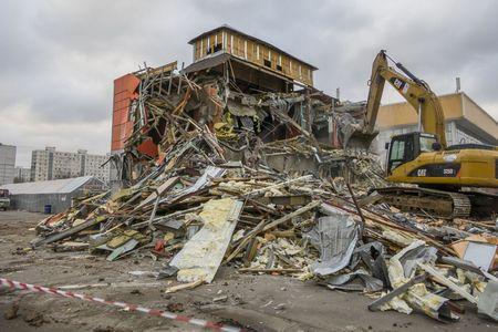 demolish: Moscow, Russia - February 11, 2016: Excavator breaks building Editorial