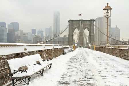 Horizontal photo of a bench on the Brooklyn Bridge during a snowstorm