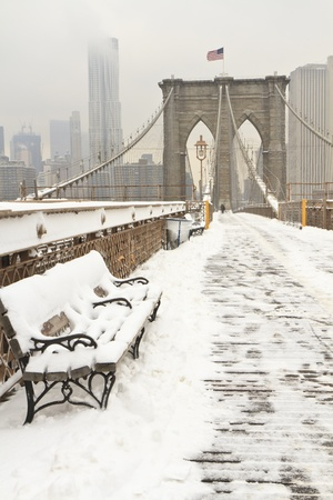 Vertical photo of a bench covered in snow on an almost empty Brooklyn Bridge Stok Fotoğraf