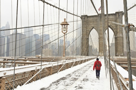 A man in a red jacket and red backpack walks across the Brooklyn Bridge in the snow photo