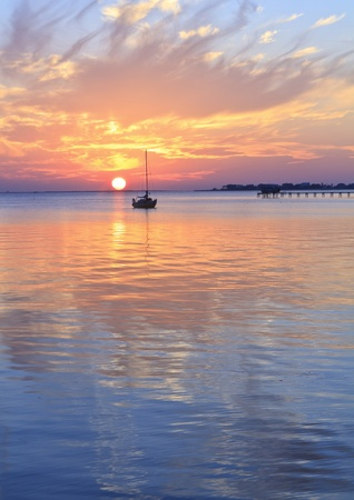 horizon reflection: A sailboat silhouetted against a brilliant sunset in a cove off Pensacola Bay, Florida