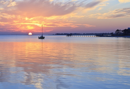 A sailboat silhouetted against a half set sun refelcted in the quiet waters of a cove off Pensacola Bay, Florida 版權商用圖片