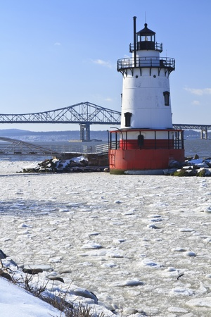 Sleepy Hollow lighthouse in front of the Tappan Zee Bridge on an icy Hudson River in New York.